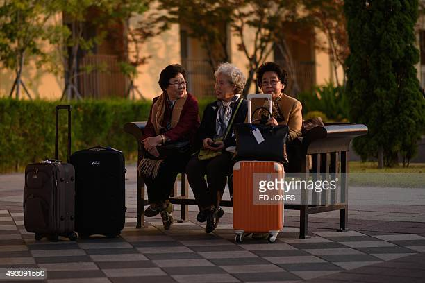 A group of South Korean women chosen to attend a family reunion event with their North Korean relatives sit on a bench outside their hotel before...