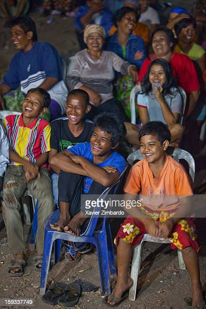 A group of spectators children and adults are loudly laughing at a night performance of Wayang Goreng by the Master Dalang Ki Mursidin during a...