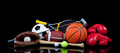 A group of assorted sports equipment on a black background with baseball supplies, soccer ball, boxing gloves, tennis ball and racket and a basketball and football