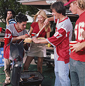 Group of sports fans grilling hot dogs at tailgate party