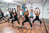 Group of sporty people exercising together with weight plates in fitness club.