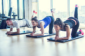 Group of sporty people exercising with legs up together at gym.
