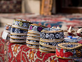 Taqiyah, traditional muslim hats placed on a typical carpet sold on a local market in Icheri Sheher (Old Town) in the Center of Baku, Azerbaijan, Caucasus. Horizontal orientation.