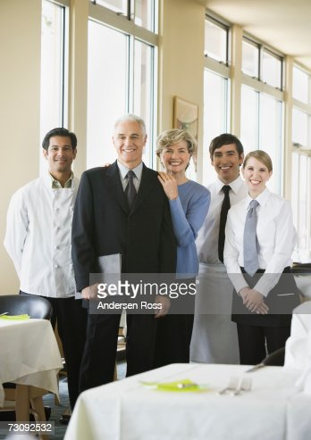 Group of staff standing in restaurant, portrait : Stock Photo