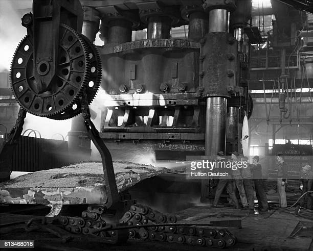 A group of steel workers from the CarnegieIllinois Steel Corporation Naval Ordnance Plant guide a hose in order to spray the coal off the armor plate...