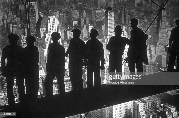 A group of steel workers standing on scaffolding 70 storeys high looking down over New York City from the RCA building