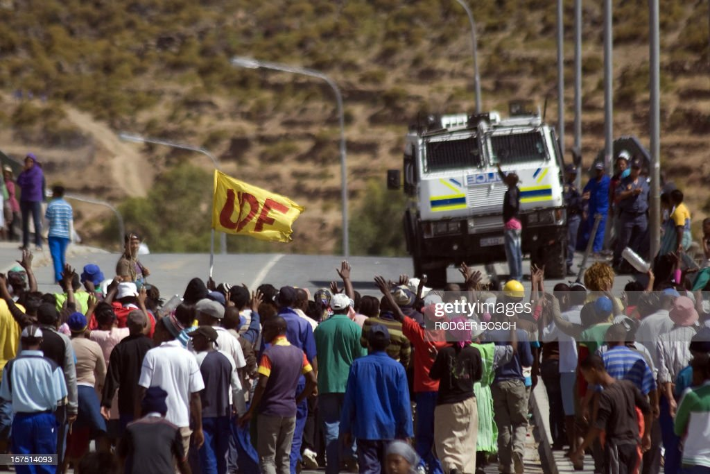 A group of striking farm workers march past a police armoured vehicle, on December 4, 2012, through De Doorns, a fruit growing region about 120Km North of Cape Town, South Africa. Workers in this region are demanding that their 70 rand ($8) wages per day be increased to 150 rand ($17). Before a two-week break for negotiations, there was violence as farmworkers in this region went on a wildcat strike, with two people being killed and millions of rand's worth of infrastructure being burnt. AFP PHOTO / RODGER BOSCH