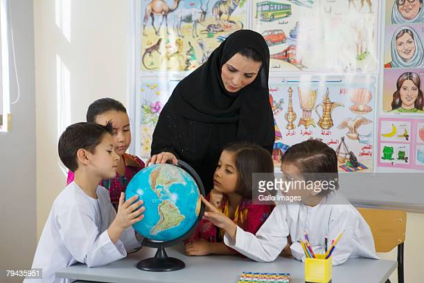 Group of students and teacher looking at globe in classroom