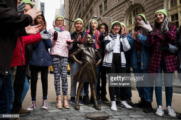 A group of students applaud after they sang Leonard Cohen's 'Hallelujah' next to the 'The Fearless Girl' statue across from the iconic Wall Street...