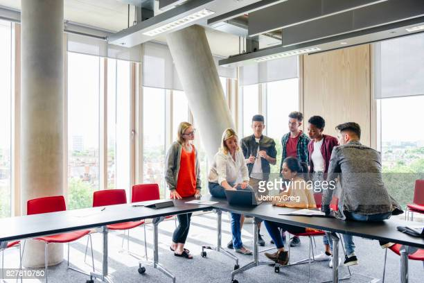 Group of students around table with laptop, teacher explaining