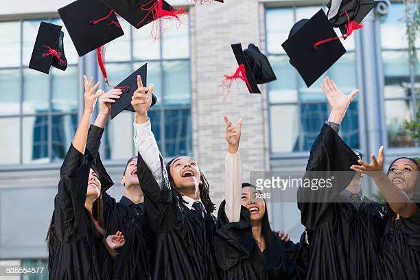 Group of students at graduation, tossing caps