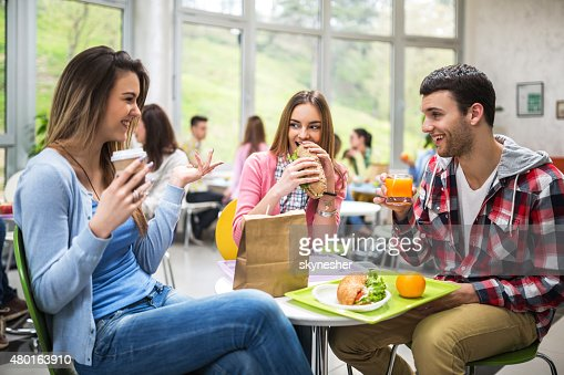 Group of students communicating during lunch in cafeteria.