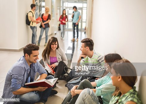 Group of students communicating on a break in school hall.