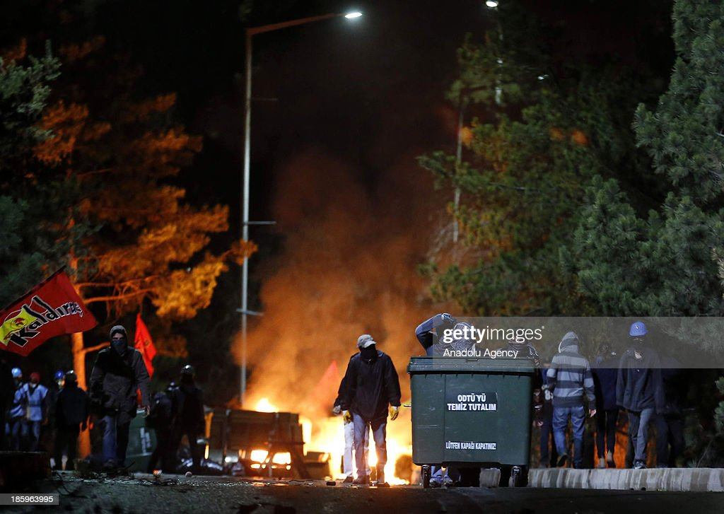 A group of students fire the barricades set afore at the A-4 entrance of Ankara's Middle East Technical University (METU) on October 26, 2013 in Ankara. Students gather to protest against the road construction which is planned to construct a new road through METU campus area. Police intervened the group with using water cannons and tear gas.