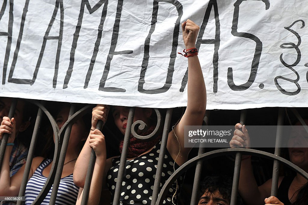A group of students from ACES (Coordinating Assembly of Secondary Students) protests after occupying the command of Michelle Bachelet during general elections in Santiago on November 17, 2013. Polls opened at 10h00 GMT, with some 9 million Chileans registered to vote. AFP PHOTO/Hector RETAMAL