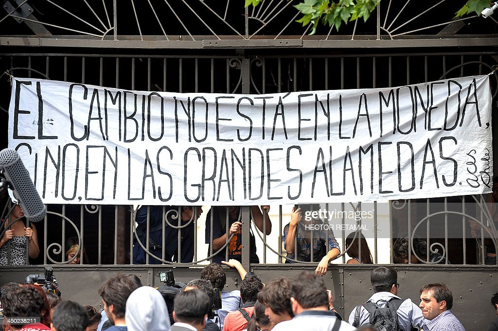 A group of students from ACES (Coordinating Assembly of Secondary Students) protests after occupying the command of Michelle Bachelet during general elections in Santiago on November 17, 2013. Polls opened at 10h00 GMT, with some 9 million Chileans registered to vote. The banner reads, 'Change isn't in La Moneda [Presidential Palace], but in the large avenues'. AFP PHOTO/Hector RETAMAL