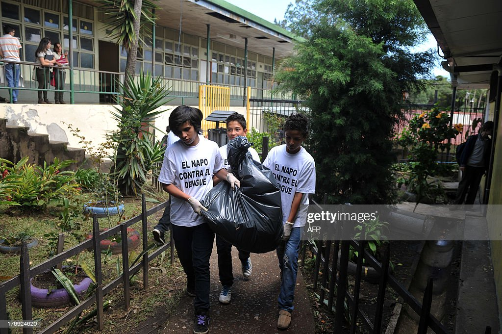 A group of students from the Napoleon Quesada secondary school clear the school yard to eliminate possible breeding sources for the Aedes aegypti mosquito that carries the virus which causes dengue, as part of the 'National Educational Crusade Against Dengue', in San Jose, on August 19, 2013. An unusually potent outbreak of dengue fever had killed at least 26 people and infected nearly 40,000 more in 2013 by July in Central America, where the mosquito-born illness is endemic. The t-shirts read 'The Napo (Napoleon Quesada secondary school) Against Dengue'. AFP PHOTO/Hector RETAMAL