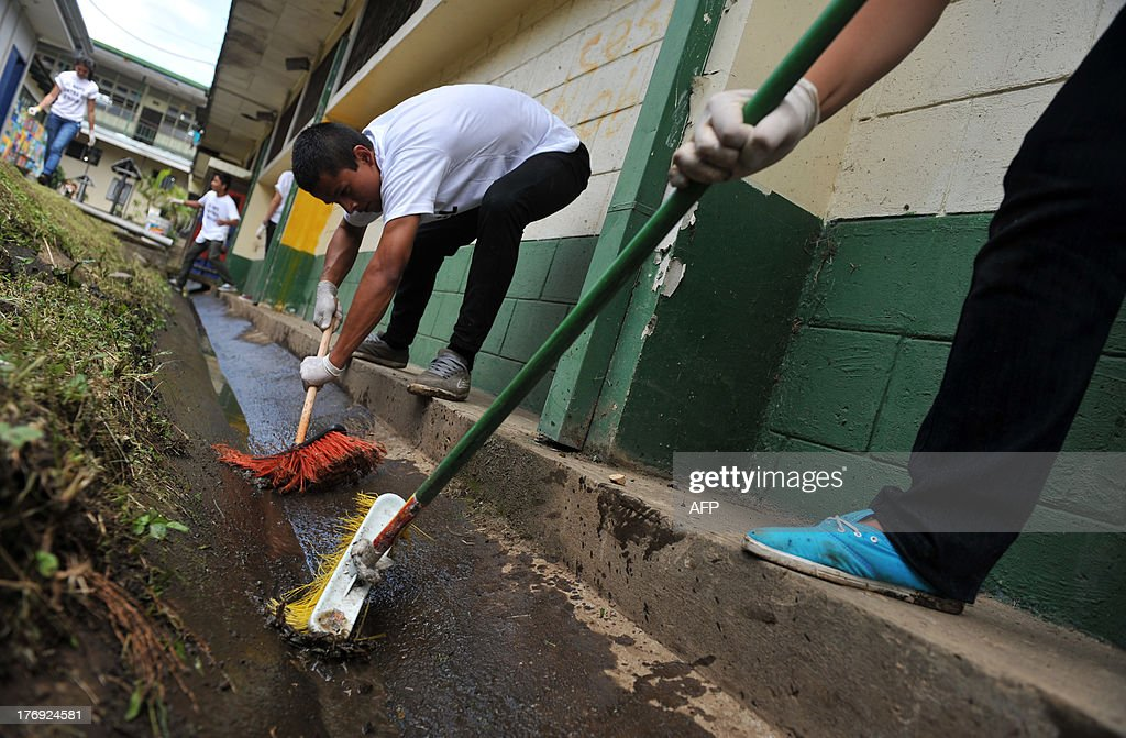 A group of students from the Napoleon Quesada secondary school wash the school yard to eliminate possible breeding sources for the Aedes aegypti mosquito that carries the virus which causes dengue, as part of the 'National Educational Crusade Against Dengue', in San Jose, on August 19, 2013. An unusually potent outbreak of dengue fever had killed at least 26 people and infected nearly 40,000 more in 2013 by July in Central America, where the mosquito-born illness is endemic. AFP PHOTO/Hector RETAMAL