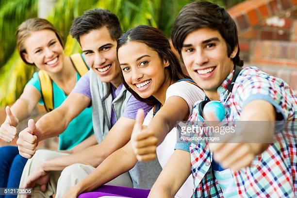 Gruppe von Studenten Gestikulieren Daumen hoch auf University Campus