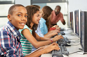 Group Of Students Working At Computers In Classroom Looking At Camera Smiling
