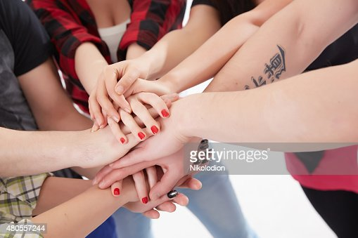 group of students in a circle of hands stacked together : Stock Photo