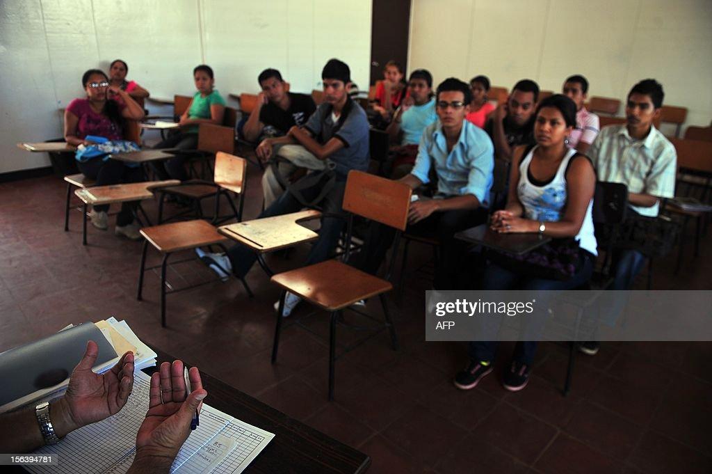 A group of students in a classroom listen to a teacher before their examination at the National Autonomous University of Nicaragua (UNAN) in Managua on November 14, 2012. AFP PHOTO/Hector RETAMAL