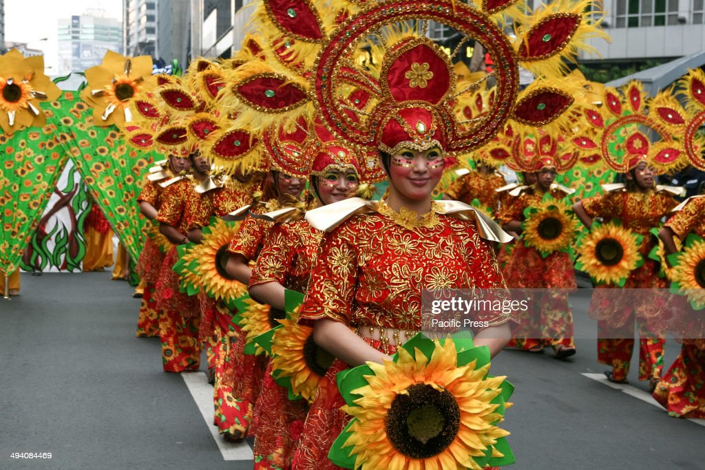A group of students in colorful costumes line up while awaiting their turn to perform during the celebration of Makati city's 344th founding anniversary. Several groups of dancers, from schools around Makati City, performed cultural dances representing local provinces of the Philippines. The students paraded along Ayala Avenue in the heart of the country's central business district.