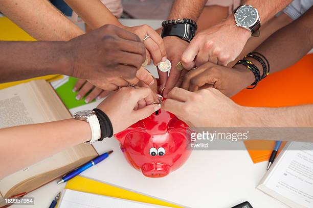 Group of students inserting coins to a piggy bank.