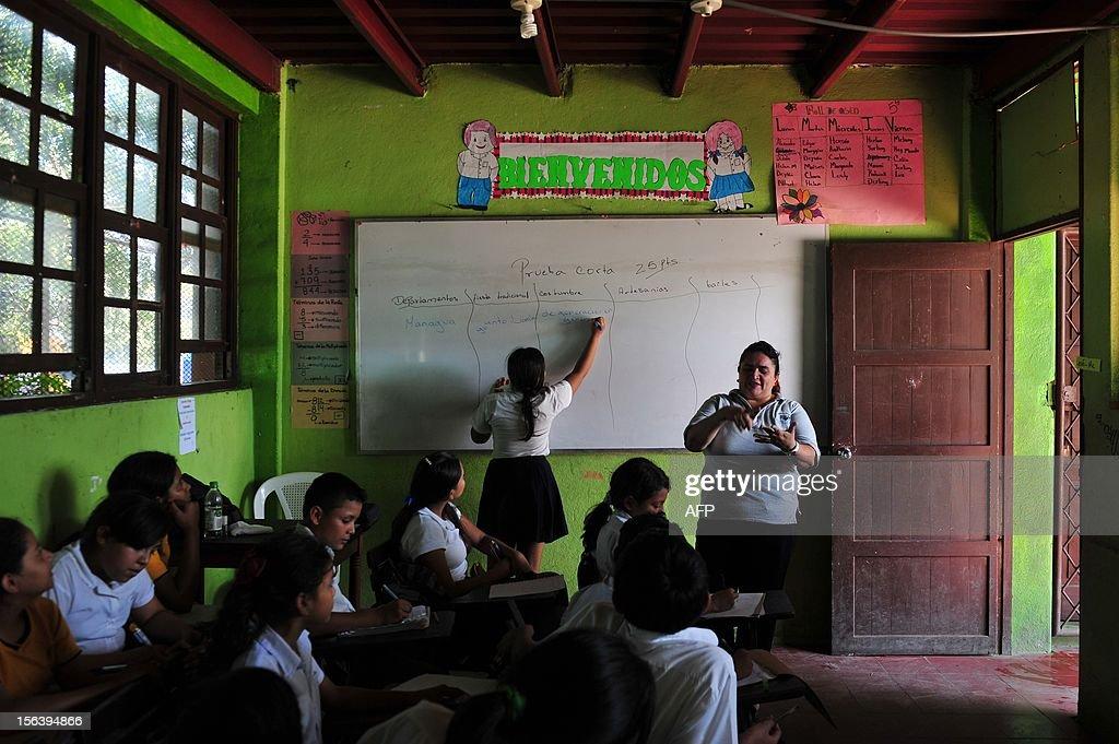A group of students listen to their teacher during a class at the 'Centro Alternativo Escuela Taller, El Proyecto' in Managua on November 14, 2012. AFP PHOTO/Hector RETAMAL