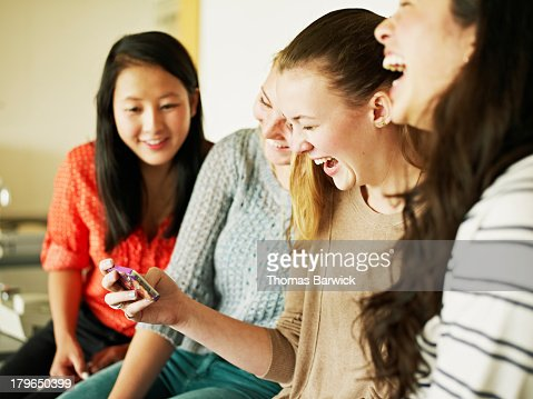 Group of students looking at smart phone laughing : Stock Photo