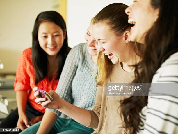 Group of students looking at smart phone laughing