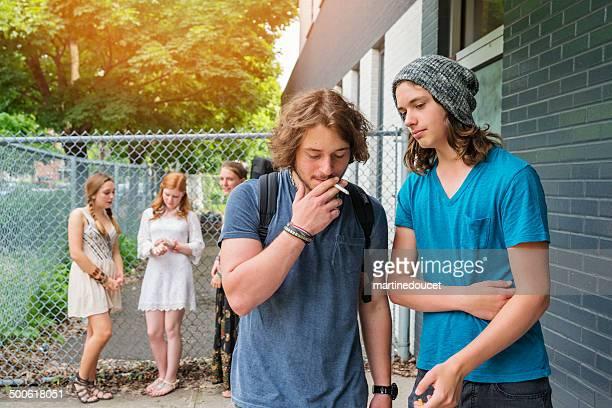 Grupo de estudiantes fuera de los establecimientos de enseñanza.  Niños son para fumadores.