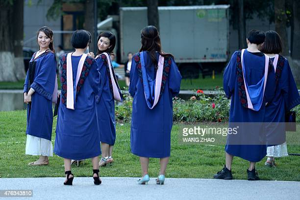 A group of students pose for photographs at a university in Beijing on June 8 2015 Despite a boom in student numbers in recent years many graduates...