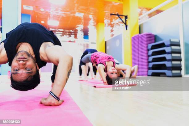 Group of students practicing wheel pose during their Yoga Class