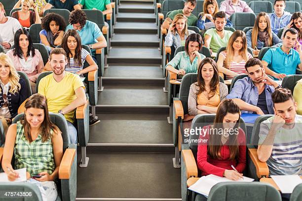 Group of students sitting in amphitheatre listening to a lecture