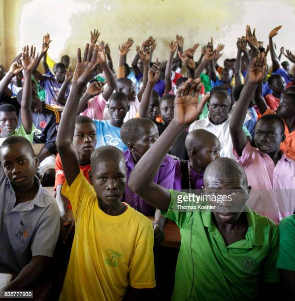 Group of students who raise their hands in a school at the Rhino Refugee Camp Settlement in northern Uganda Here children of local people and...