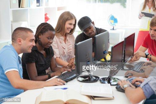 Grupo de estudiantes trabajando juntos en ordenadores.