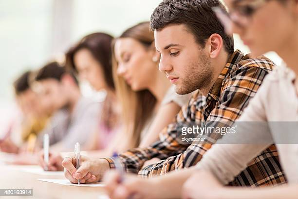 Group of students writing during a lecture.