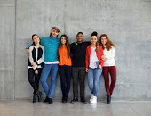 Group of stylish young university students on campus. Multiracial young people standing together against wall in college.