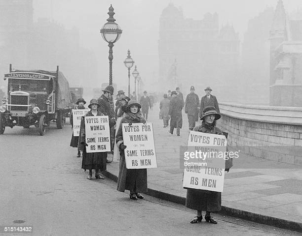 A group of suffragists picket outside the House of Commons Presently a bill is being passed giving women the right to vote at the age of 21