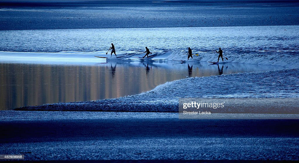 A group of surfers ride the Bore Tide at Turnagain Arm on July 14, 2014 in Anchorage, Alaska. Alaska's most famous Bore Tide, occurs in a spot on the outside of Anchorage in the lower arm of the Cook Inlet, Turnagain Arm, where wave heights can reach 6-10 feet tall, move at 10-15 mph and the water temperature stays around 40 degrees Fahrenheit. This years Supermoon substantially increased the size of the normal wave and made it a destination for surfers.