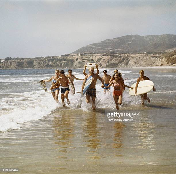 Group of surfers running in water with surfboards, smiling