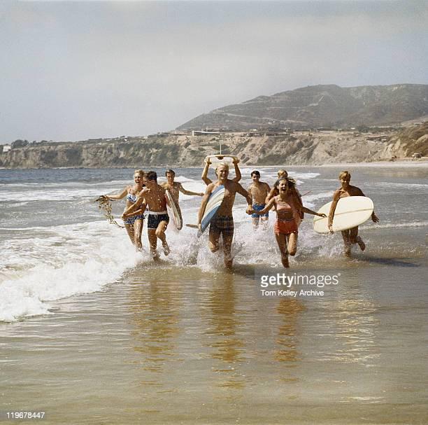 Groupe de surfers courant dans l'eau avec des planches de surf, souriant