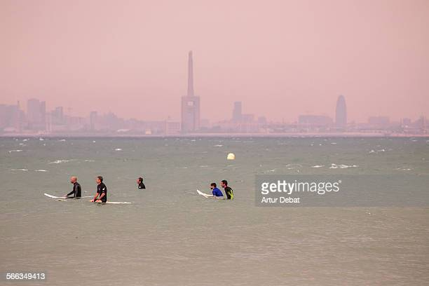 Group of surfers waiting for the waves in the Barcelona shoreline with the city views Masnou Catalonia Europe