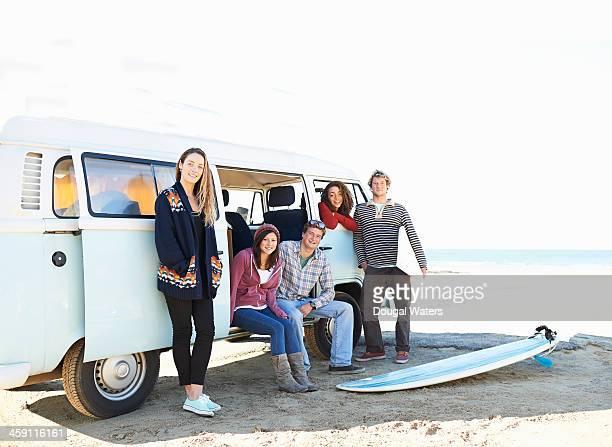 Group of surfers with camper van beside beach.
