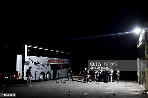 A group of Syrian refugees and migrants board a bus to travel from Presevo to Belgrade late on August 30 2015 Migrants and refugees pass through the...