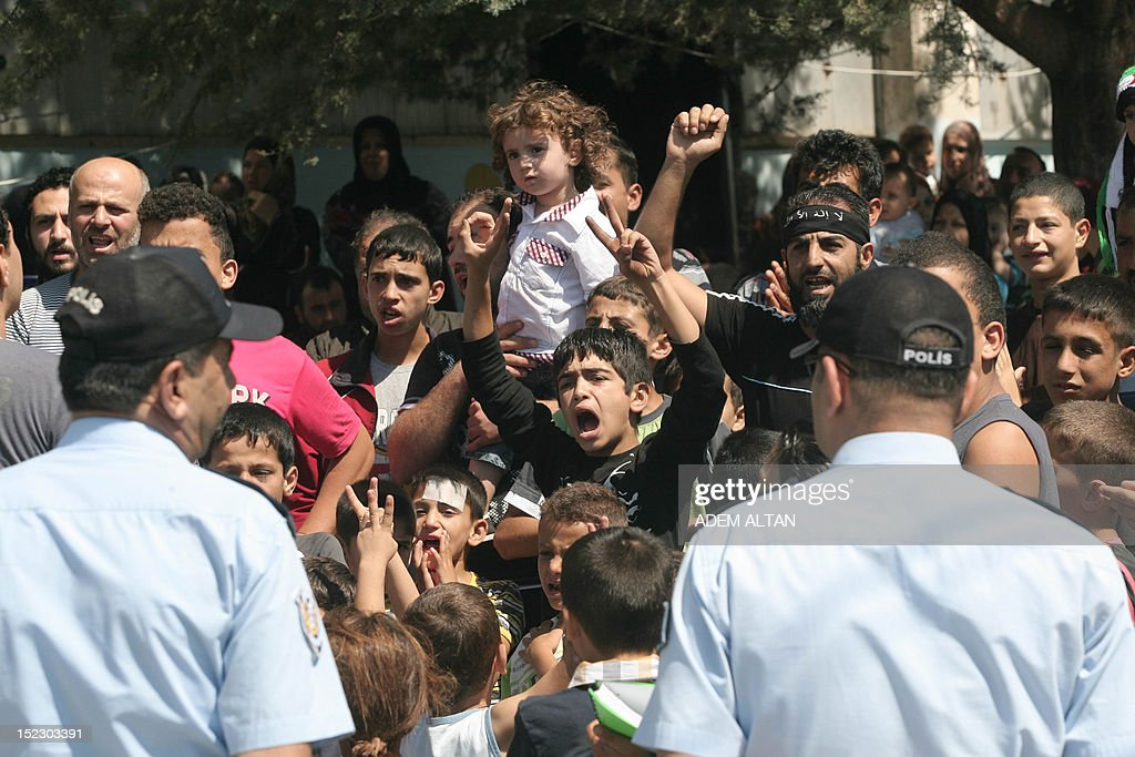 A group of Syrian refugees chant slogans 'freedom to syria' as International peace envoy for Syria arrives in the Altinozu camp in Hatay city, located on the border with their violence-racked homeland, on September 18, 2012. The Altinozu camp is one of the first refugee camps set up by Turkey soon after the unrest erupted in Syria mid-March 2011, which has already killed 20,000 according to UN figures and forced 250,000 to flee into neighbouring countries. AFP PHOTO / ADEM ALTAN