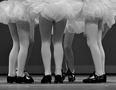 Close up of a group of young tap dancers legs during a performance