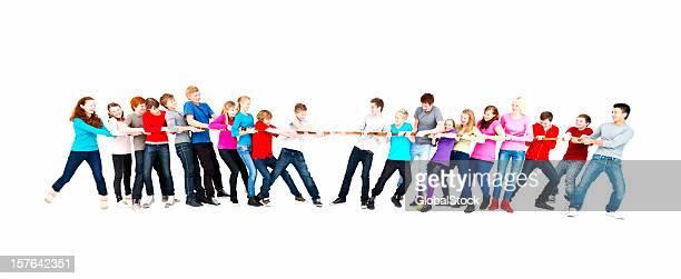 A group of teenage boys and girls playing tug of war