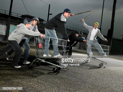Group of teenage boys (13-15) racing with shopping trolleys : Stock Photo